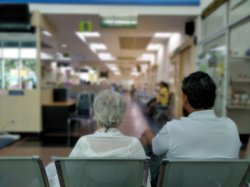 De oude vrouw en de volwassen man zitten op het grijze roestvrije stoel wachten medisch en gezondheidsdiensten aan het ziekenhuis royalty-vrije stock foto