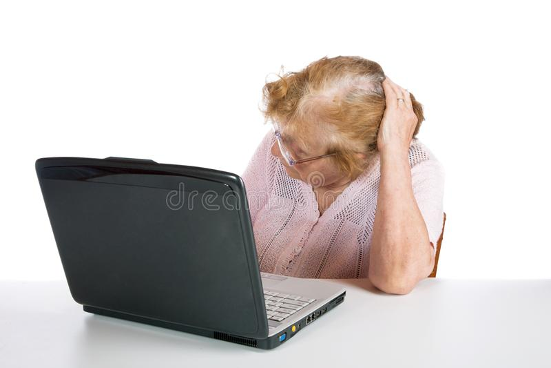 De oude vrouw in glazen bekijkt het het schermnotitieboekje stock afbeelding
