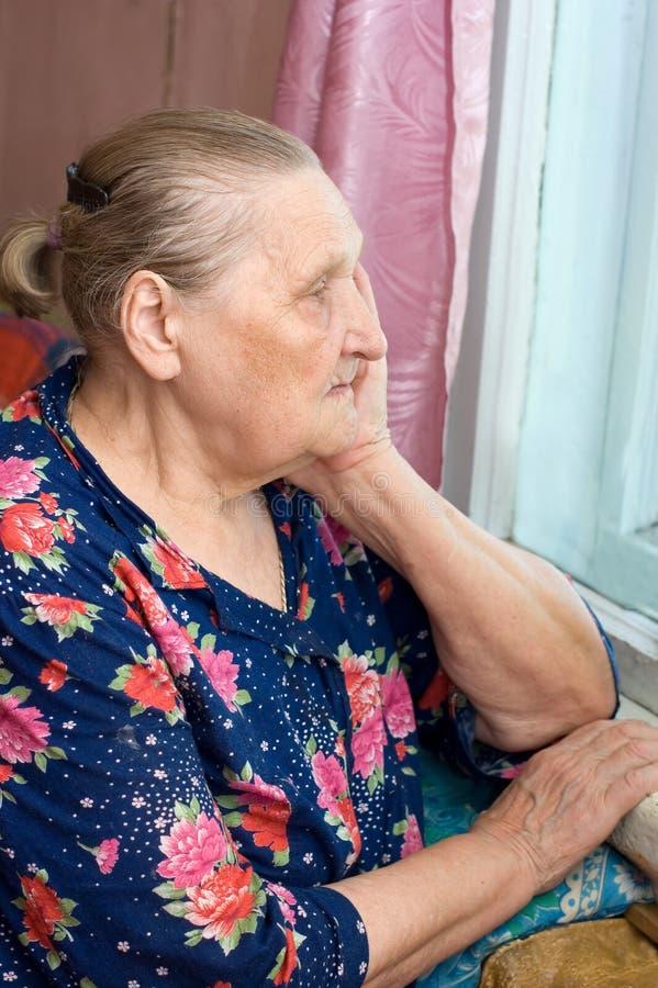 De oude vrouw kijkt uit het venster stock fotografie