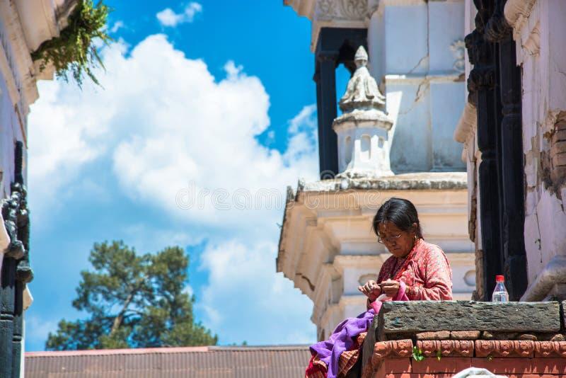 De oude vrouw naait kleren in de Pashupatinath-Tempel 13 April 2018 stock foto's