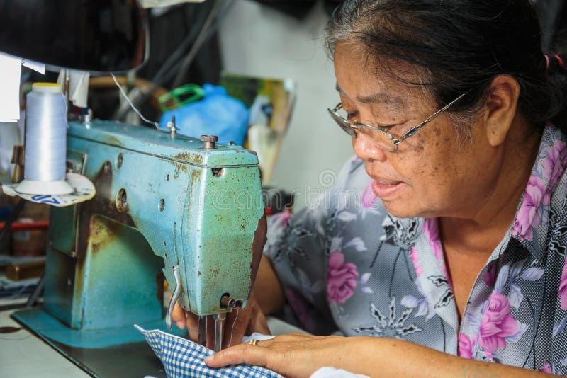 De oude vrouw naait op de naaimachine in de straat stock foto