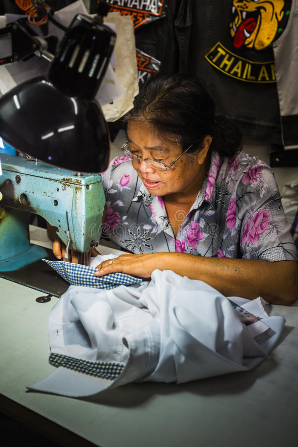 De oude vrouw naait op de naaimachine in de straat stock afbeelding