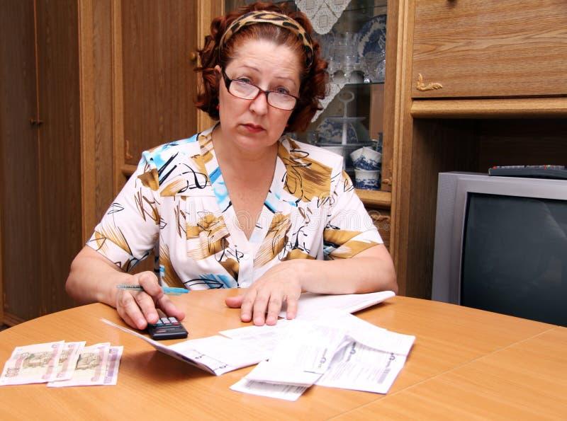De oude vrouw telt geld stock afbeelding