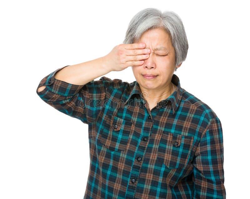 De oude vrouw voelt oog geworden pijn stock foto's