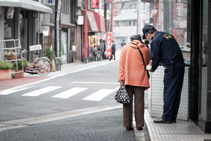 De oude vrouw vraagt om richting van een politie op de straat van Japan stock foto