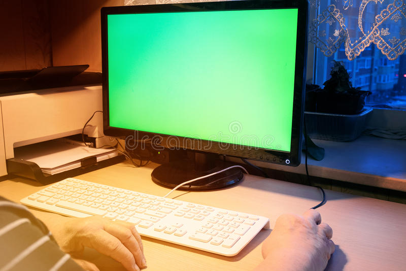 De oude vrouw werkt thuis aan computer, met het groene scherm, uw tex stock afbeeldingen