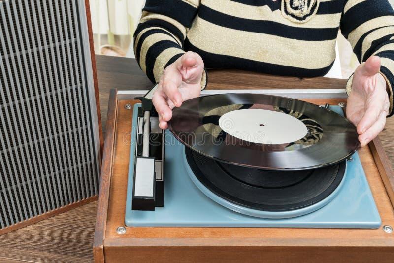 De oude vrouw zet een vinylverslag stock foto's