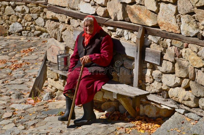 De oude vrouw zit langs steenmuur royalty-vrije stock fotografie