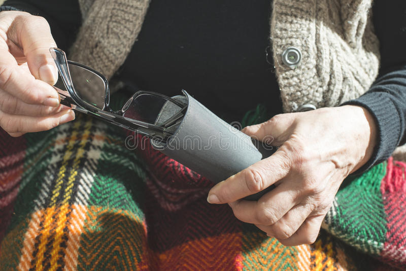De oude vrouwen houden glazen stock foto