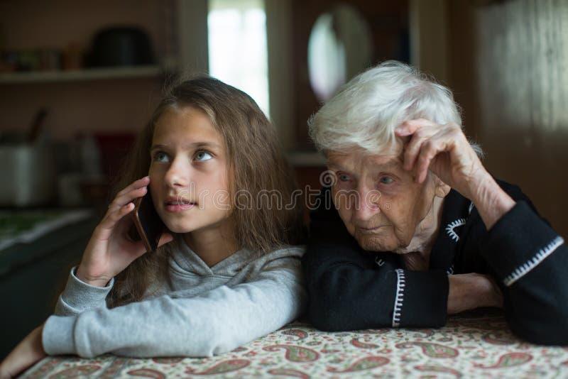 De oude vrouwengrootmoeder luistert als kleindochter van een klein meisje die op een mobiele telefoon spreken Familie royalty-vrije stock afbeelding
