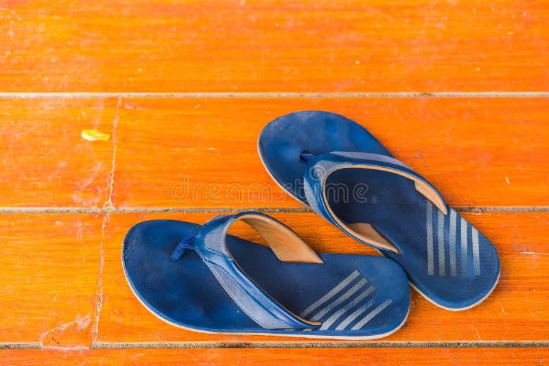 De Oude, vuile rubberschoenen op de oranje vloer Hoogste mening en exemplaarruimte stock afbeelding