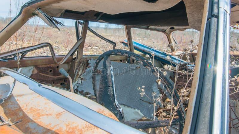 De oude wijnoogst roestte uit auto verlaten in het midden van geen waar het bos van Wisconsin - dat na het registreren bos wordt  stock foto