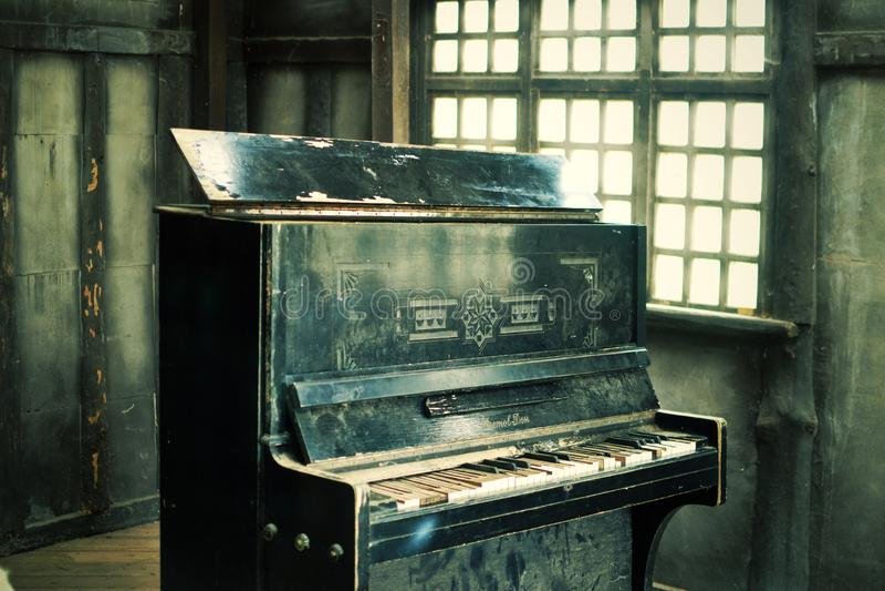 De oude zwarte gebroken piano stock foto