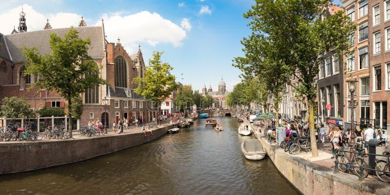 De Oudekennissteeg-brug met de kerk van Oude Kerk, Amsterdam stock afbeelding