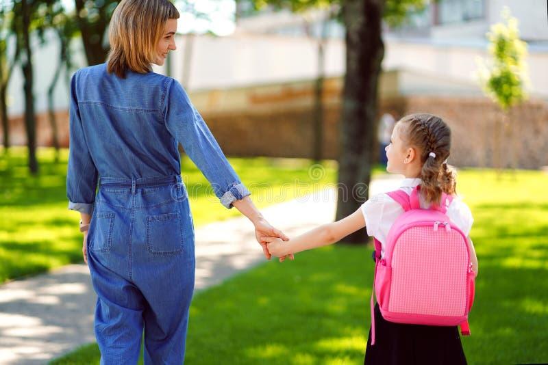 De ouder en de leerling van lage school gaan hand in hand Vrouw en meisje met rugzak achter de rug Begin van lessen stock foto's