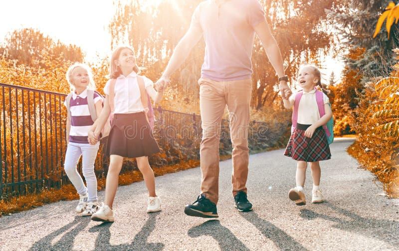 De ouder en de leerlingen gaan naar school stock foto