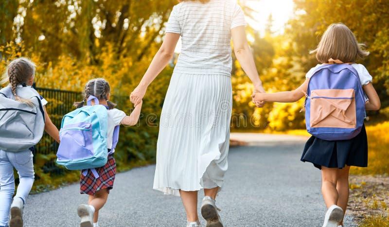 De ouder en de leerlingen gaan naar school stock afbeelding