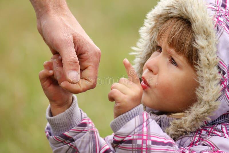 De ouder houdt de hand van een kind stock afbeelding