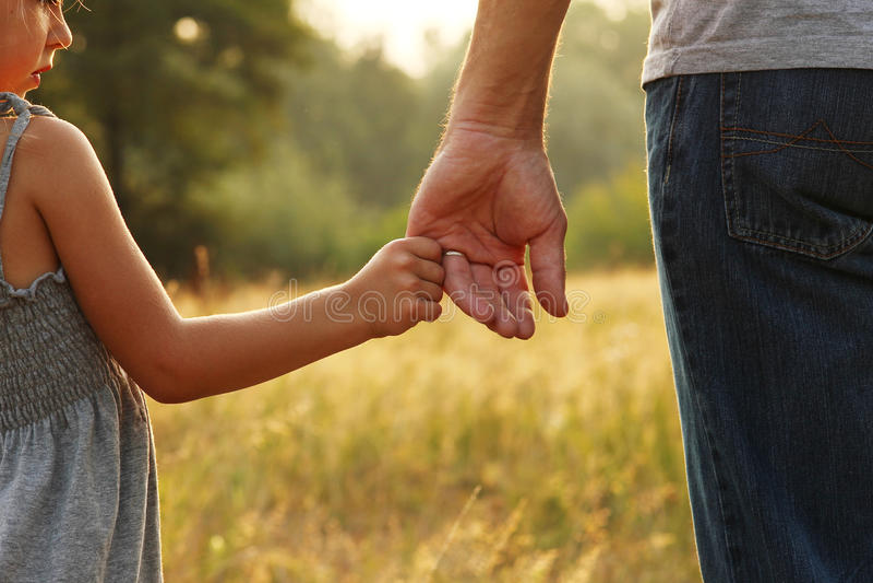 De ouder houdt de hand van een klein kind royalty-vrije stock afbeeldingen