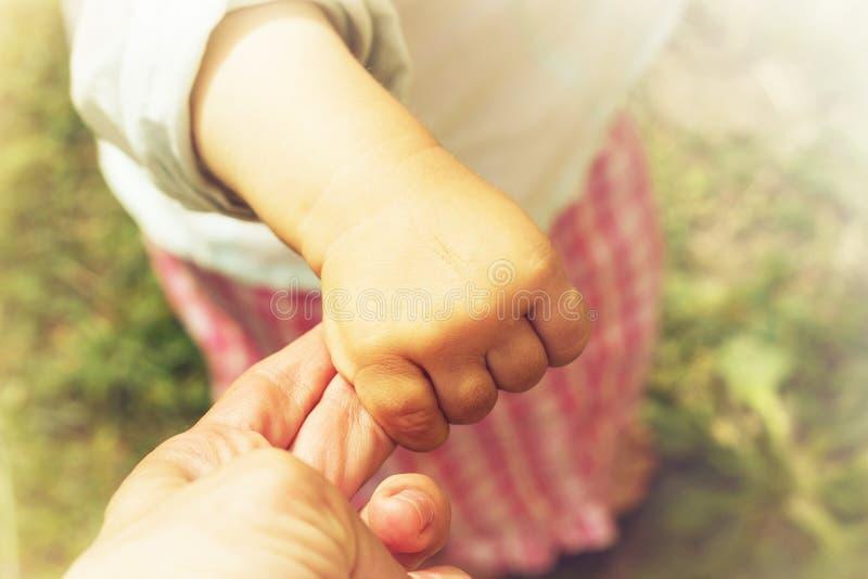 De ouder houdt de hand van een klein kind gestemd stock foto's