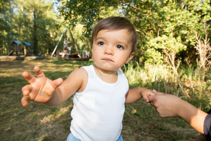 De ouder houdt de hand van een kleine kindjongen stock afbeelding