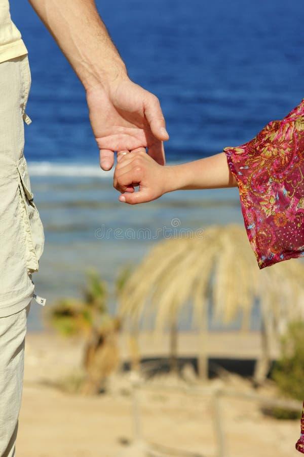 De ouder houdt de hand van het kind op het strand stock foto