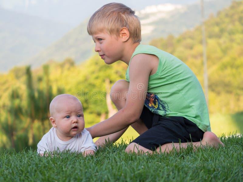De oudere broer kalmeert de baby, die bang wordt gemaakt royalty-vrije stock afbeelding