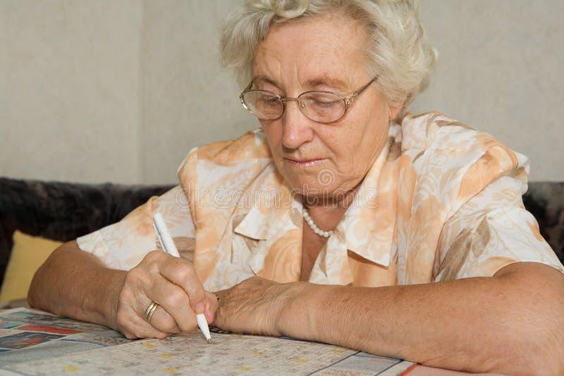 De oudere dame lost geheimzinnigheid op stock afbeeldingen