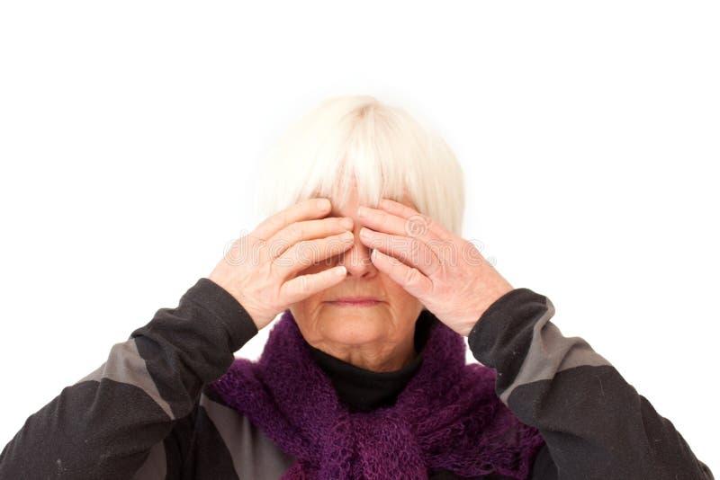 De oudere dame met overhandigt haar ogen stock fotografie