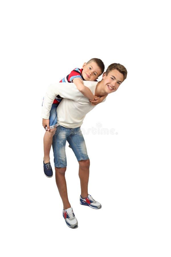 De oudere jongen vervoert weinig broer op rug stock foto's