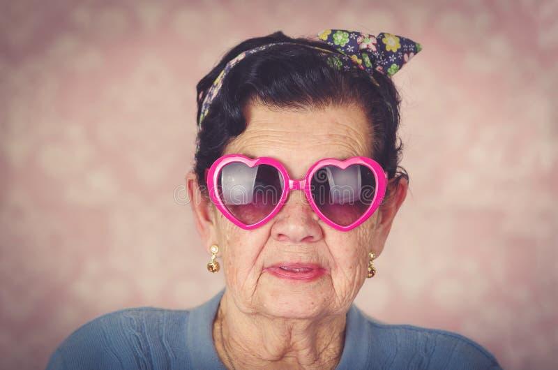 De oudere koele Spaanse vrouw die blauwe sweater, de boog van het bloempatroon op hoofd en roze dragen heartshaped zonnebril het  stock fotografie