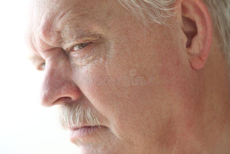De oudere mens is boos of verdacht stock foto
