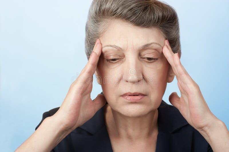 De oudere vrouwen hebben een hoofdpijn stock afbeelding