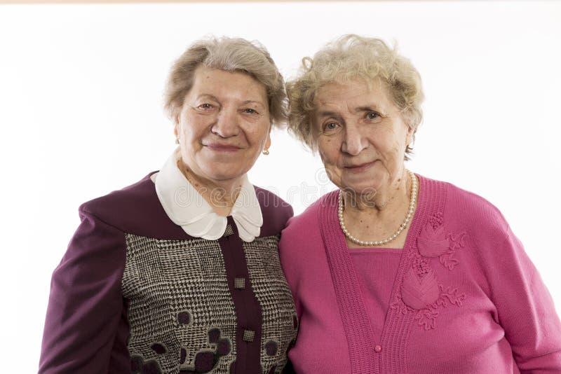 De oudere vrouwenvrienden omhelzen en lachen, close-up stock foto
