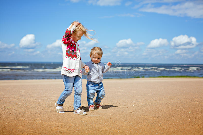 De oudere zuster en de jongere broer Blonds lopen langs zijn royalty-vrije stock afbeeldingen