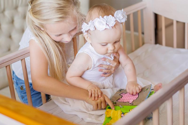 De oudere zuster toont het boek aan de babyzuster royalty-vrije stock fotografie
