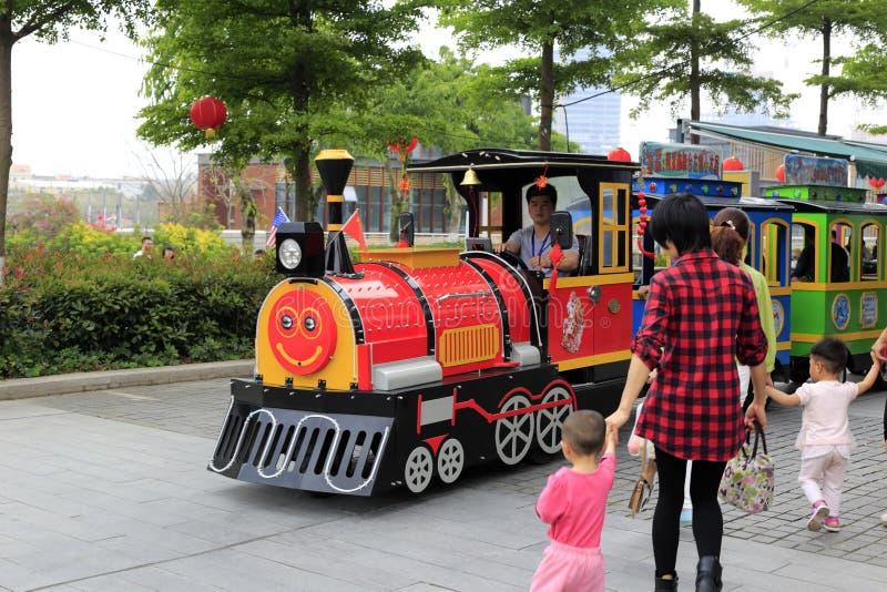 De ouders brengen het kind om op een grote stuk speelgoed trein te zitten stock foto's