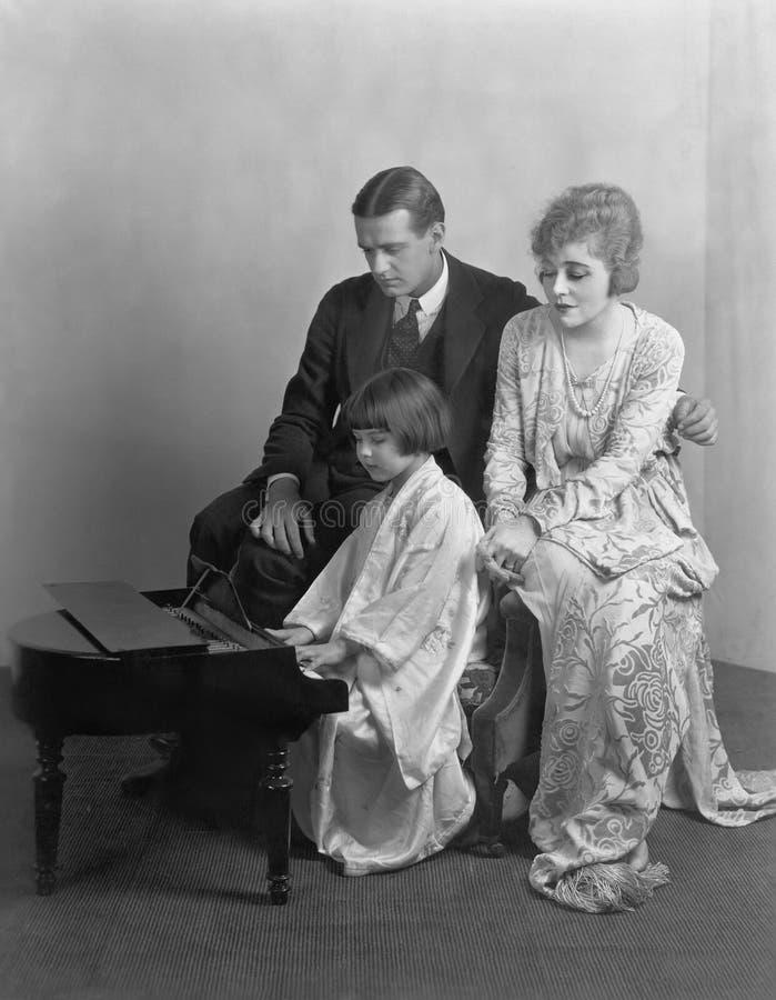 De ouders die aan dochter luisteren spelen miniatuurpiano (Alle afgeschilderde personen leven niet langer en geen landgoed bestaa stock afbeeldingen