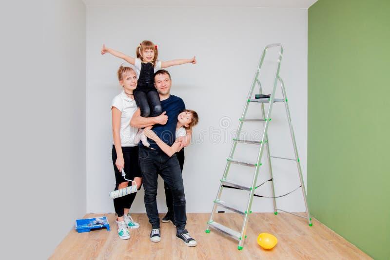 De ouders en de kinderen zijn verf een nieuwe ruimte stock foto's