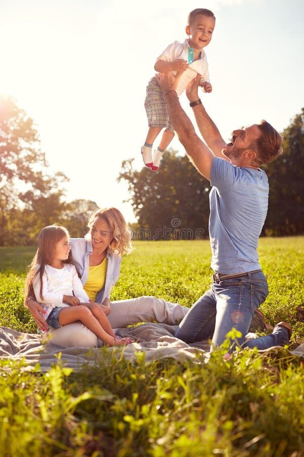 De ouders hebben pret met kinderen op picknick royalty-vrije stock foto