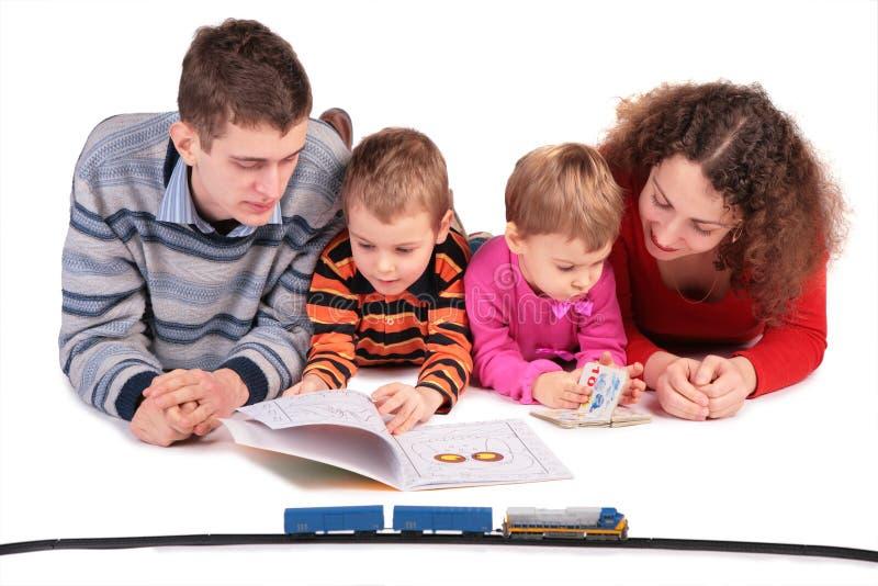De ouders kijken boeken met kinderen stock afbeelding