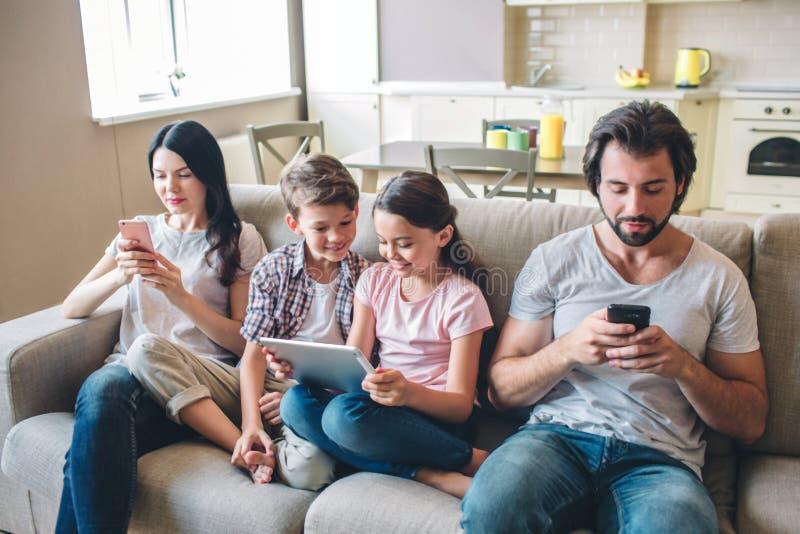 De ouders zitten op bank met jonge geitjes en bekijken telefoons De kinderen zijn bettween binnen vrouw en de mens Het meisje hou royalty-vrije stock foto's
