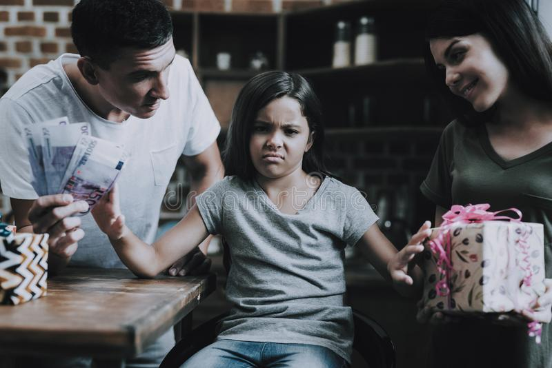 De oudersglimlach en geeft Bored Meisje Heldere Giften royalty-vrije stock afbeeldingen