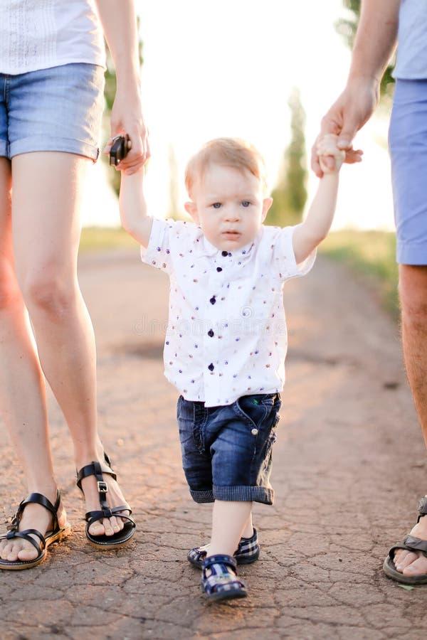 De oudershanden van weinig mannelijke kindholding en het lopen op weg stock afbeeldingen