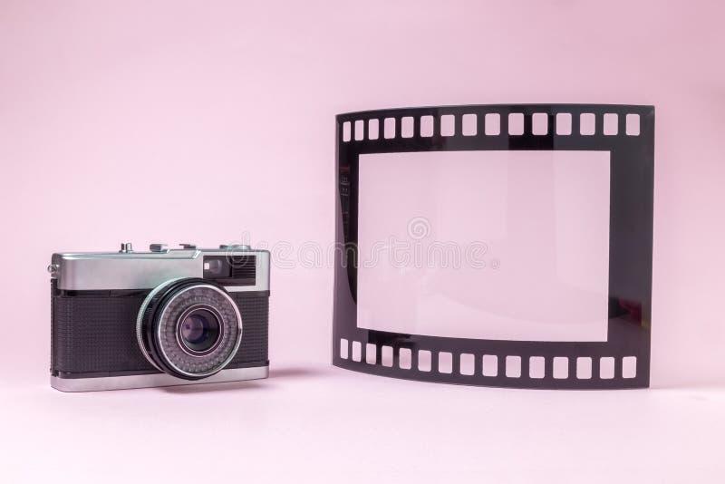 De ouderwetse fotografiecamera en het fotokader in vorm van filmband rollen op duidelijke roze achtergrond stock afbeeldingen