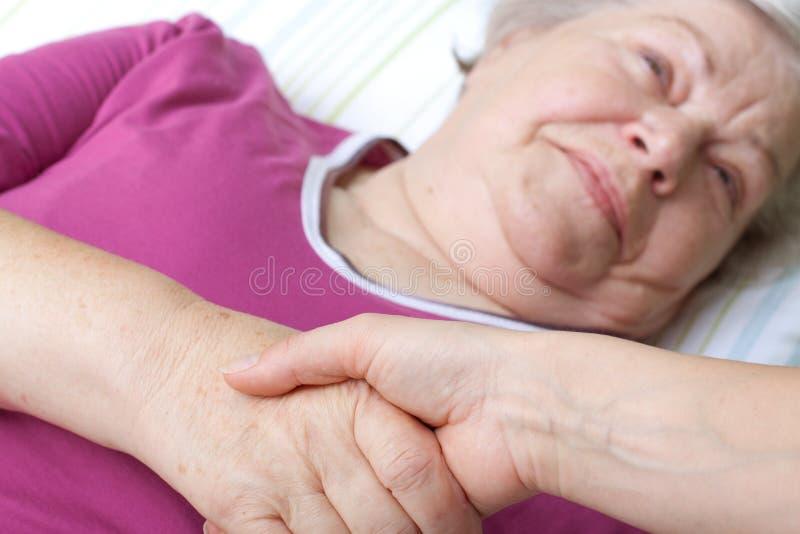 De oudste die in bed ligt en heet verpleegster welkom royalty-vrije stock afbeeldingen