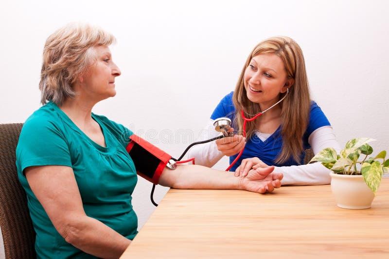 De oudste van verpleegstersmaatregelen de bloeddruk stock foto