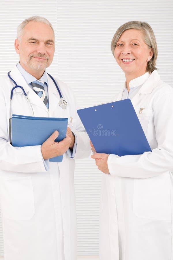 De oudsten die van het medische artsenteam greepomslagen glimlachen stock afbeelding