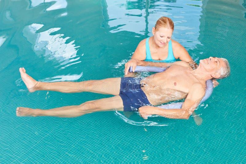 De oudsten doen yoga in het zwembad stock foto