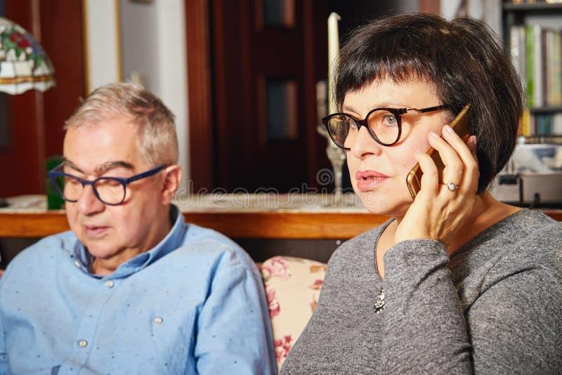 De oudsten koppelen zitting op de laag terwijl vrouw het spreken op de telefoon royalty-vrije stock foto